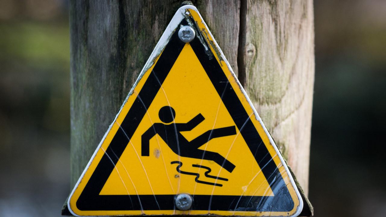 Skilt som viser en person som sklir og faller. Foto