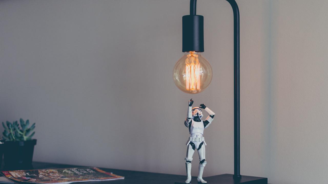 Foto: En liten robot strekker seg opp mot en lyspære i en lampe