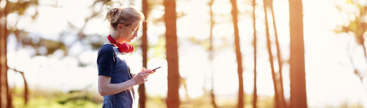 Ung dame med hodesett ser på en mobilskjerm mens hun står ute i solskinnet. Foto