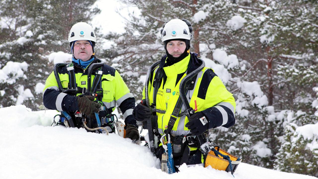 To energimontører står med snø til livet i fullt arbeidsantrekk. Foto