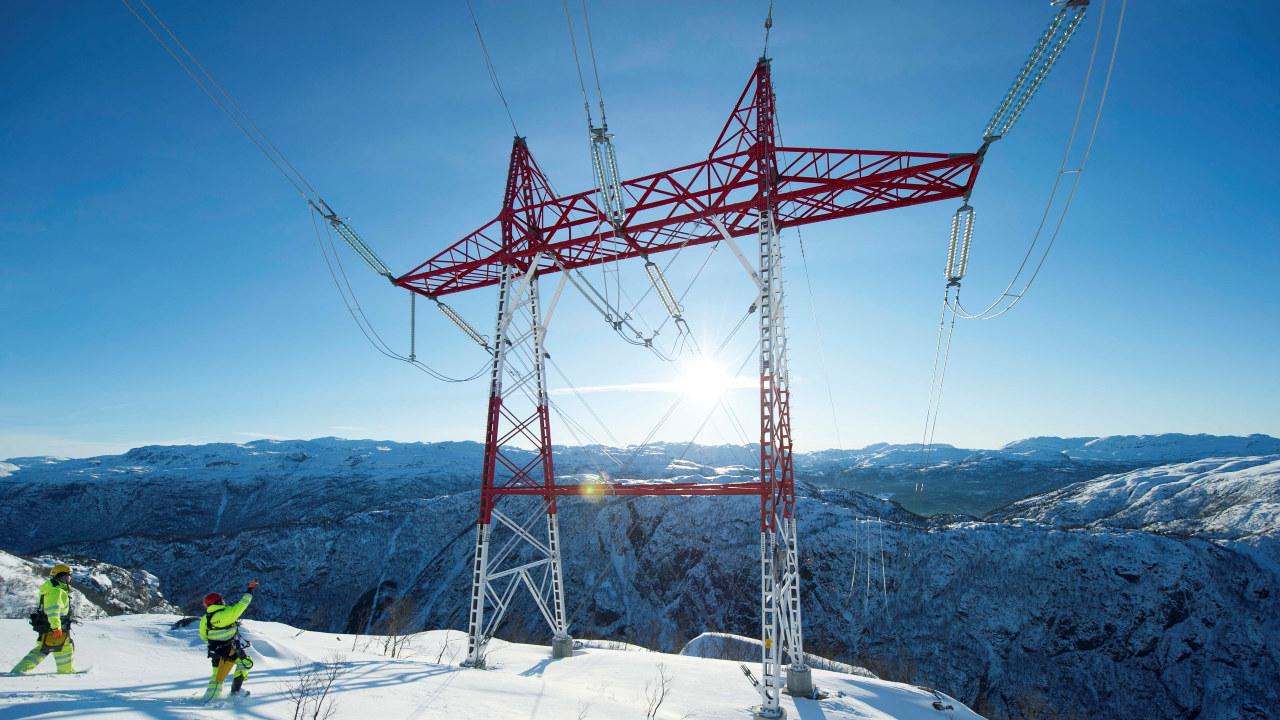 To menn på en snøkledd fjelltopp og en strømmast
