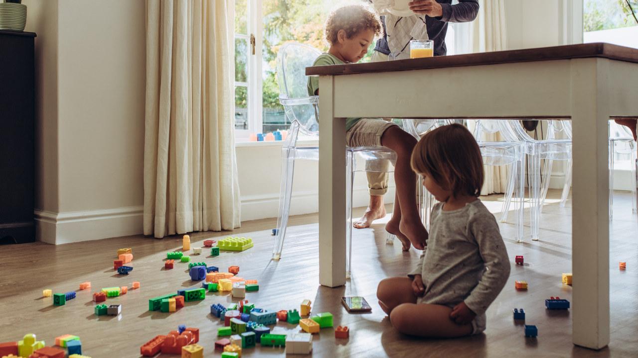 En mann tørker opp en tallerken mens et barn spiser og et barn leker. Foto