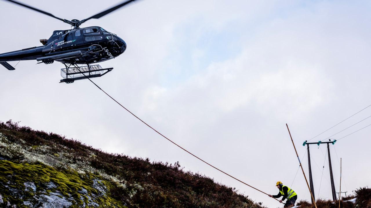 Helikopter og en mann som jobber med en kraftmast. Foto