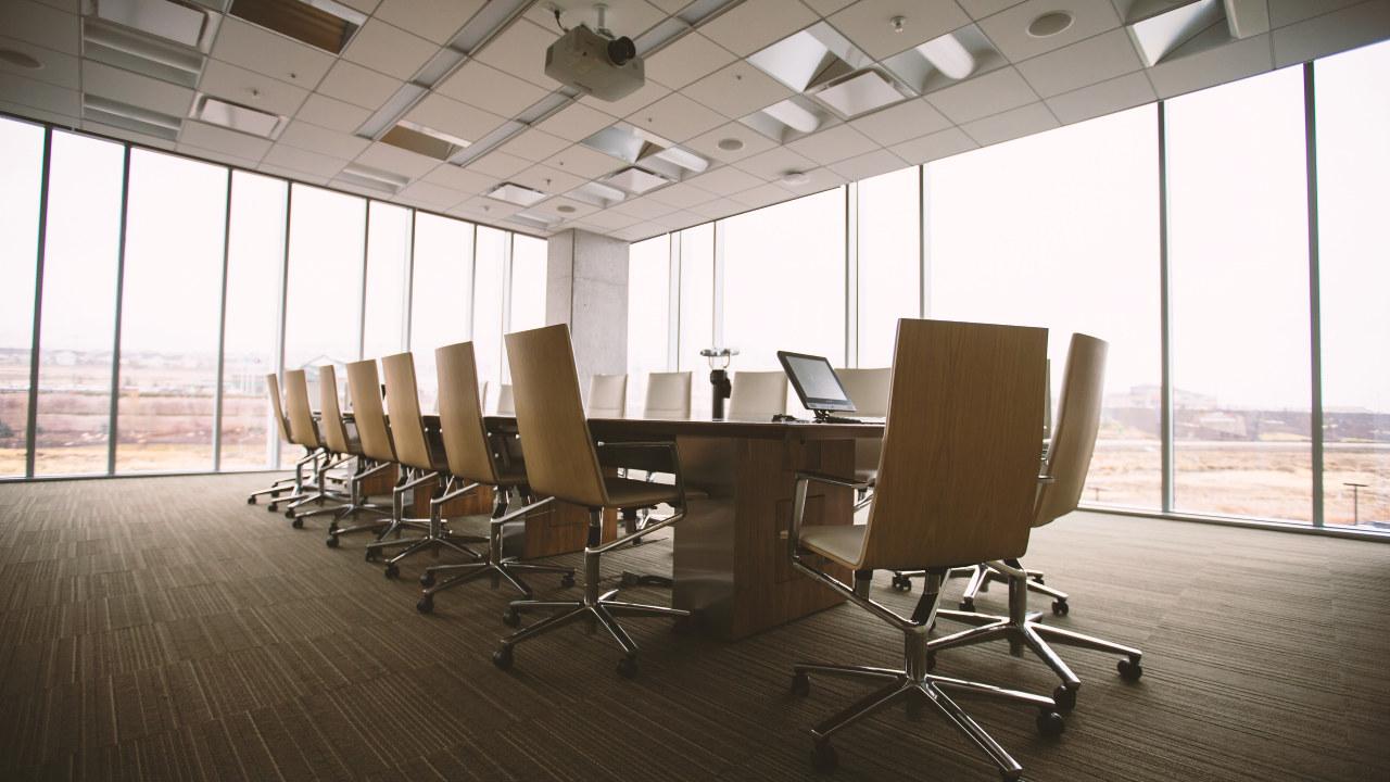 Et møterbord med stoler rundt omkranset av store vinduer. Foto