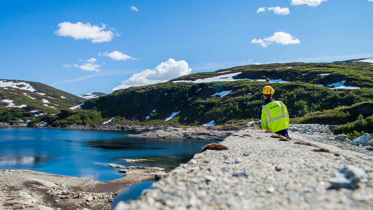 Mann i vernedress og hjelm ser utover en dam. Foto