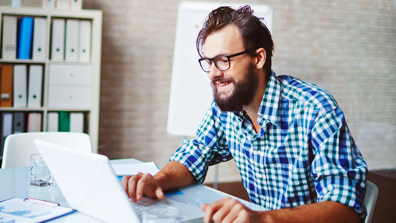 Young businessman in casualwear using laptop in office papirarbeid