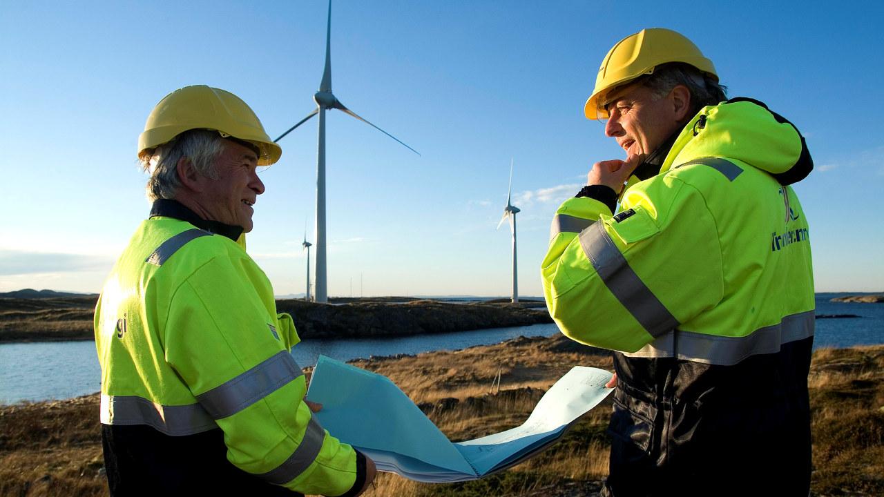 Bilde av to menn med hjelm og vernetøy som snakker sammen over et kart foran vindmøller.