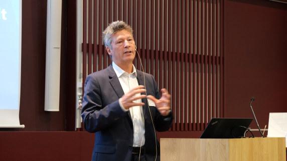 Foto: Anders Sivertgård står og snakker på en scene.