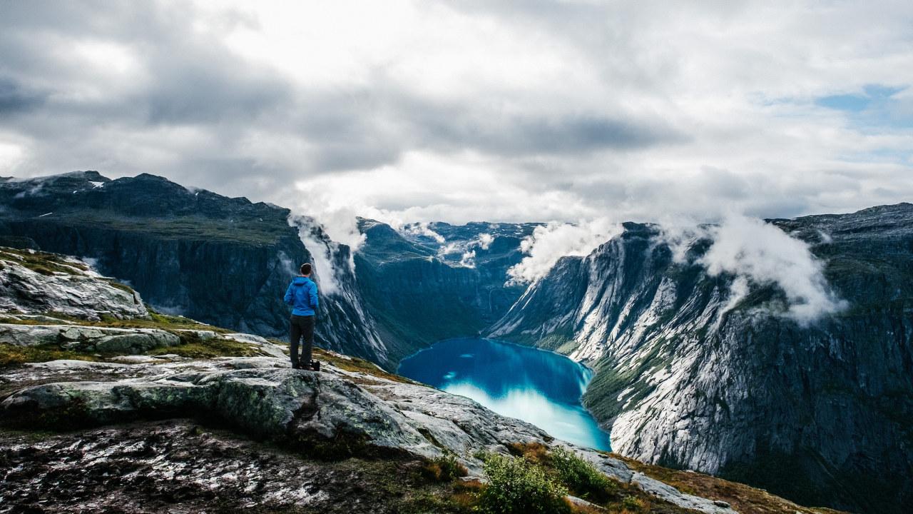 Foto: Mann står og ser ut over Tyssedal fra et fjell og ned mot et vann.