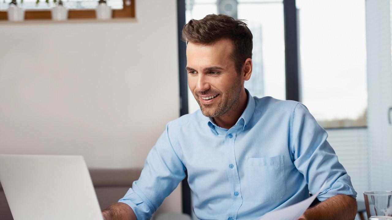 Lagre og returner Bredde  1280 px Høyde  720 px  Bilde av en glad mann som sitter foran en PC og betaler regninger