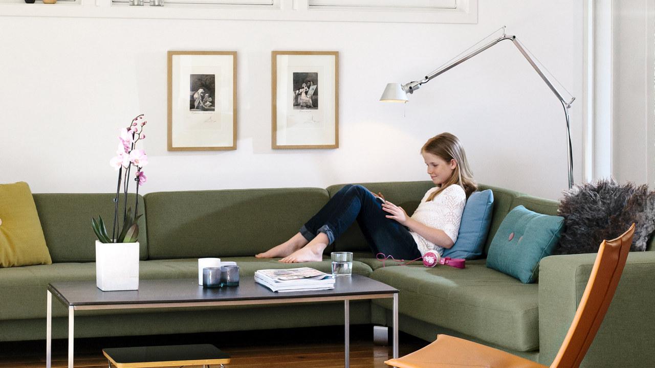 Foto: Jente sitter i sofaen under en lampe og leser.