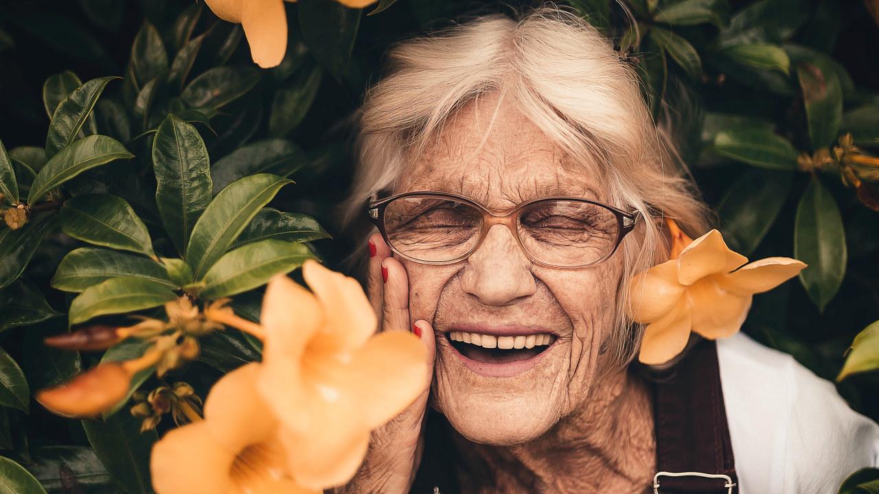 Foto: Dame står nærme en busk med gule blomster