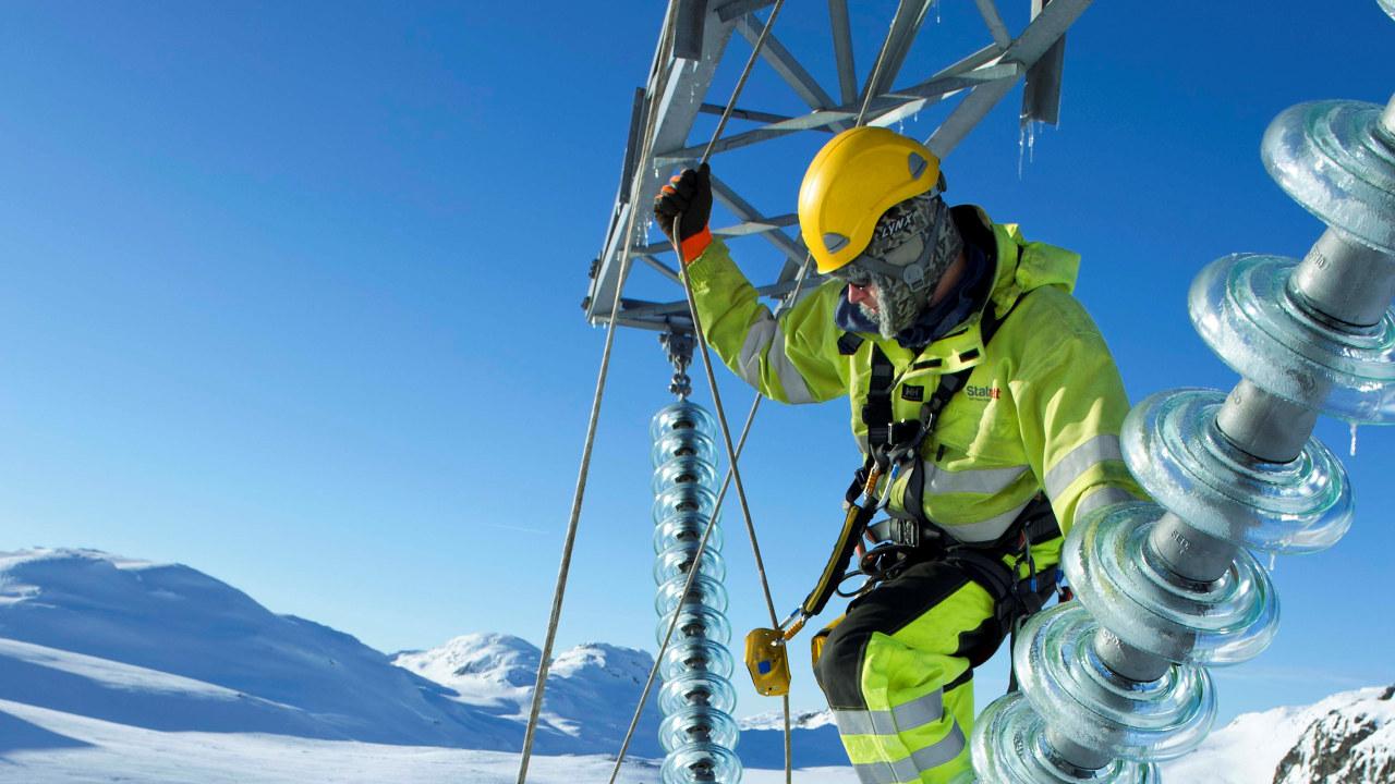 Foto: En energimontør arbeider  i en kraftmast om vinteren med snø.