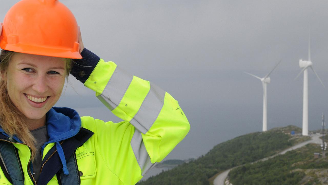 FotoDame holder en hånd på hjelmen sin. Vindmøller i bakgrunnen.