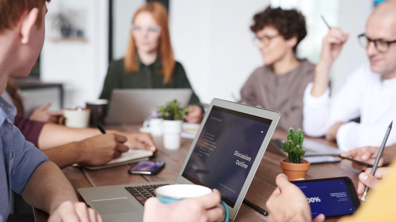 Foto: Mennesker rundt et arbeidsbord med PC.