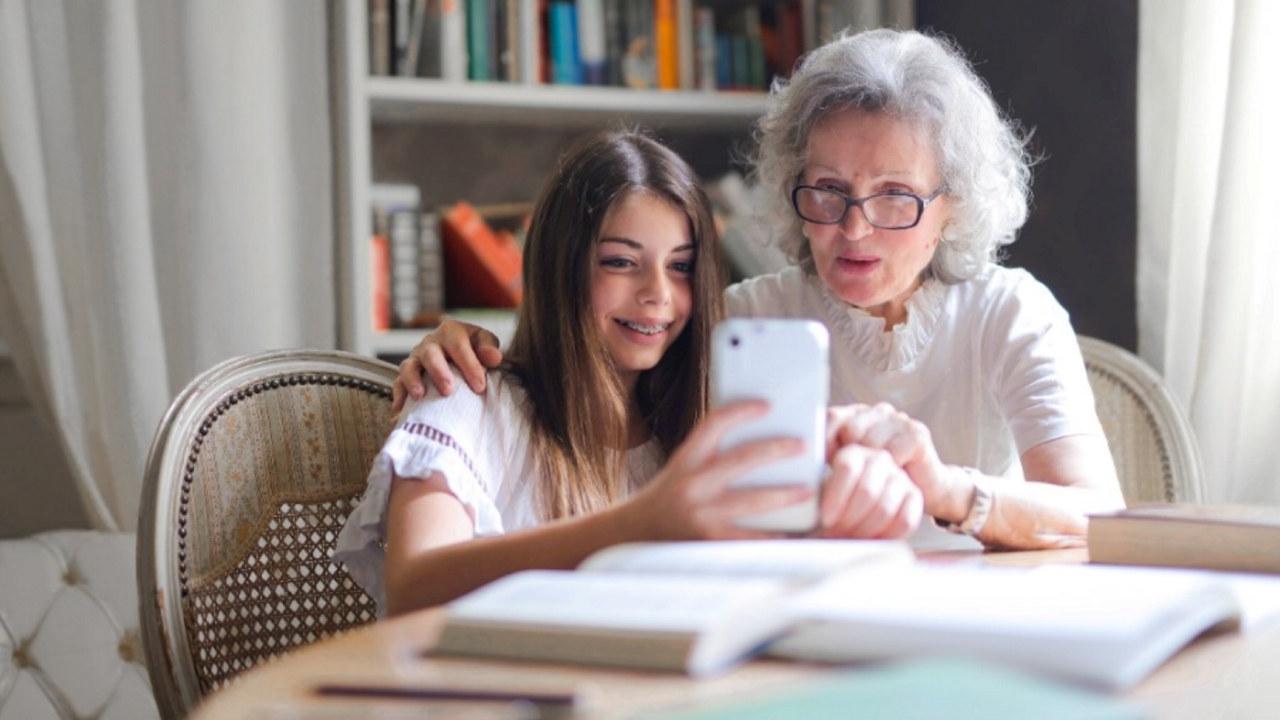 Foto: En jente og en eldre dame sitter sammen og ser på en mobilskjerm