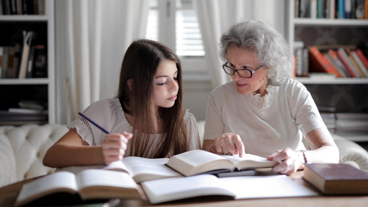 Foto: En jente og en eldre dame sitter sammen og seri en bok.
