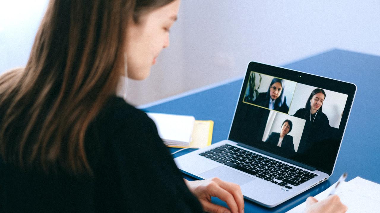 Foto: Dame med langt hår sitter foran en PC skjerm med bilder av tre damer.