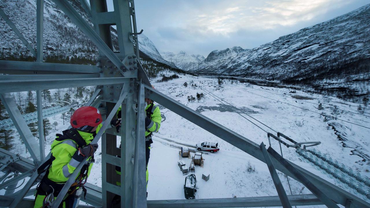 Foto: To energimontører arbeider i en kraftmast