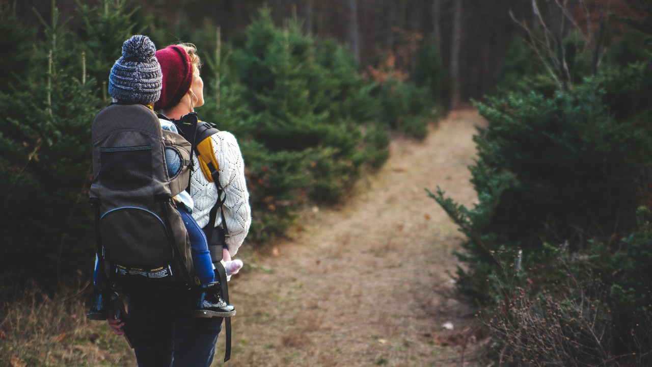 Foto: Dame med barn i sele på ryggen på tur i skogen.