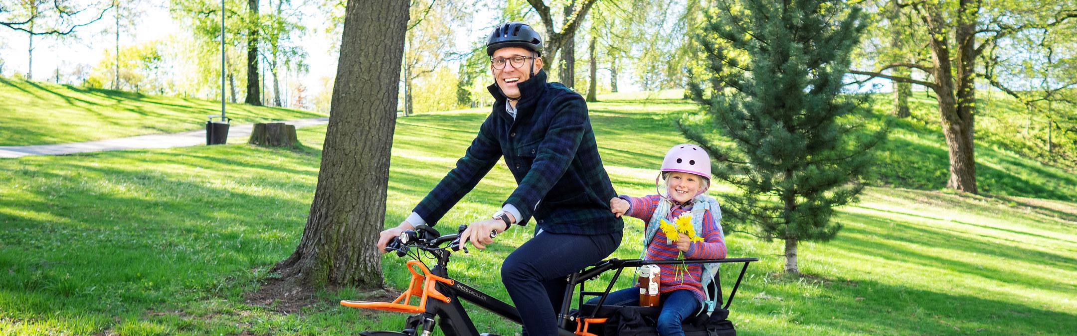Foto: En mann sykler på en elsykkel med en jentunge som sitter bakpå