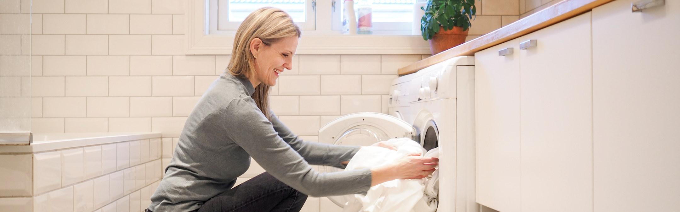 Foto: Dame med langt lyst hår sitter på huk foran en vaskemaskin med sengetøy.
