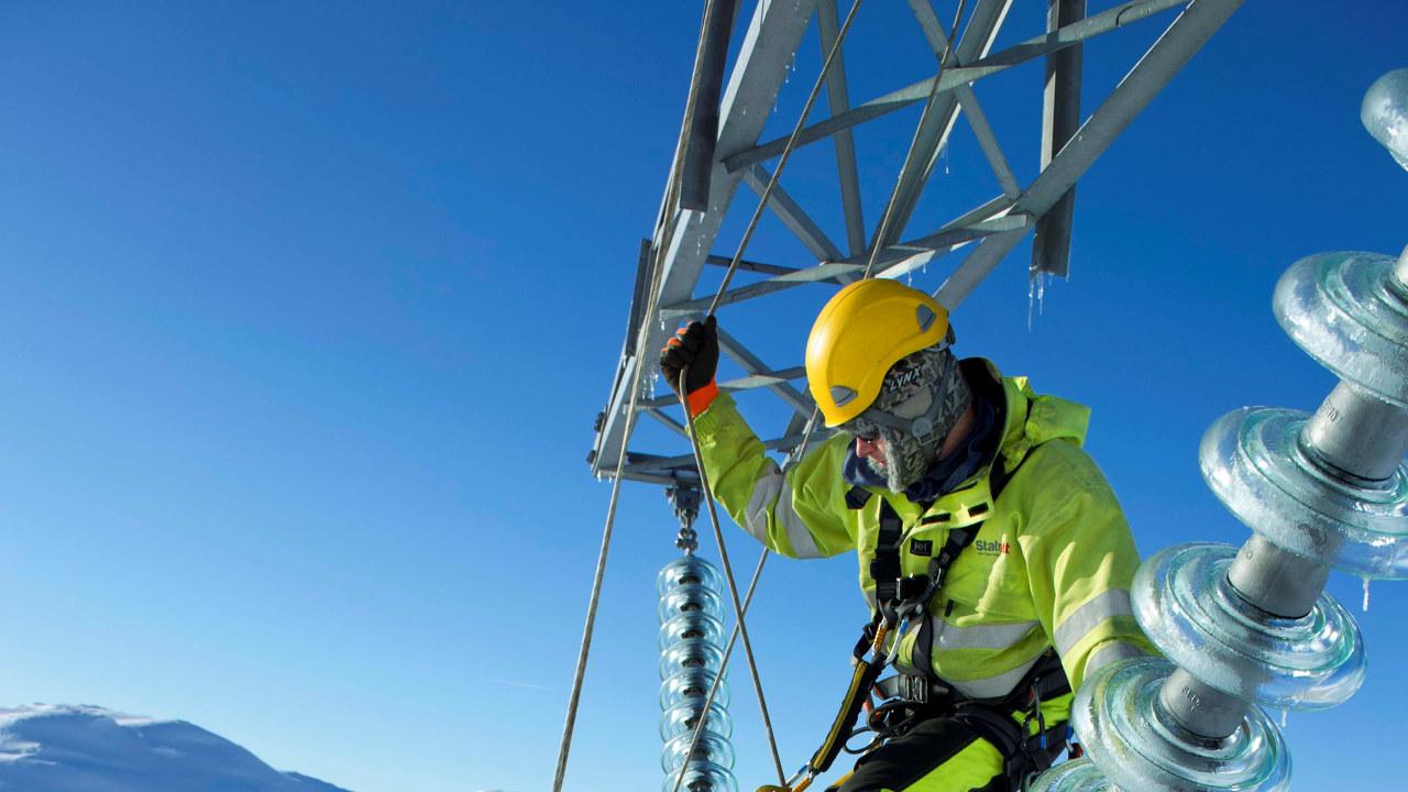 Foto: En energimontører arbeider i en kraftmast