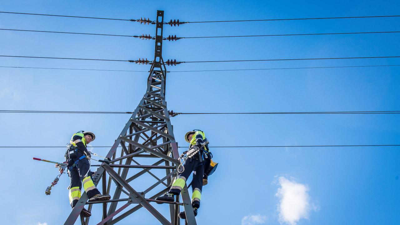 Foto: to energimontører i en kraftmast