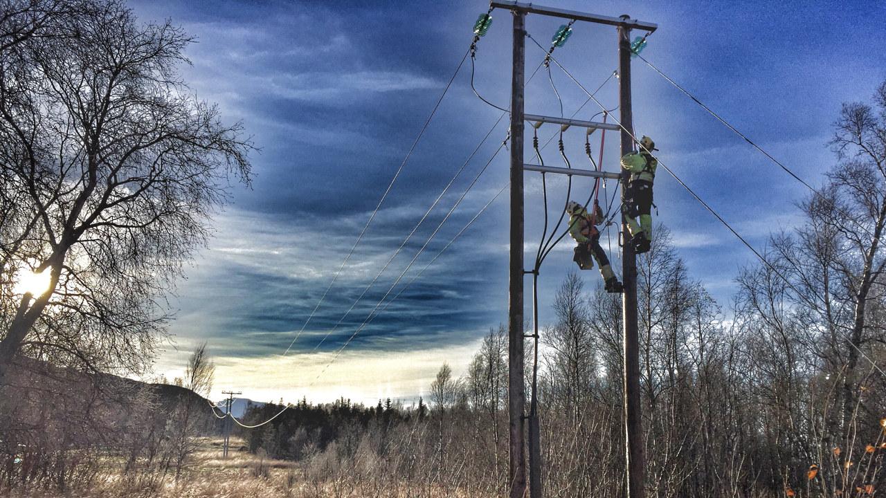 To energimontører klatrer i en strømmast og det er frost på bakken. Foto