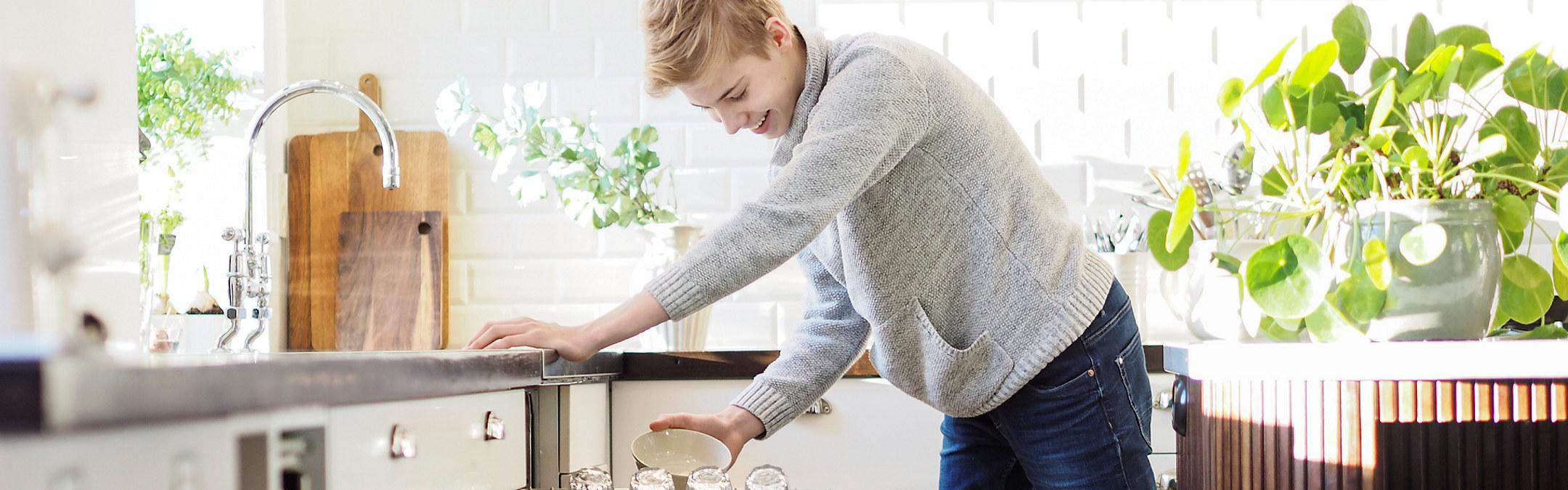 Ung blond gutt rydder ut av oppvaskmaskin. Foto
