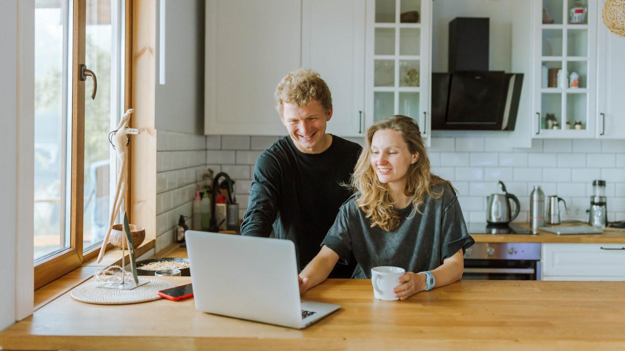 En mann og en dame er på kjøkkenet og ser på en PC. Foto