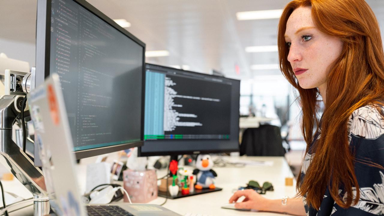 Dame jobber foran flere PC skjermer. Foto