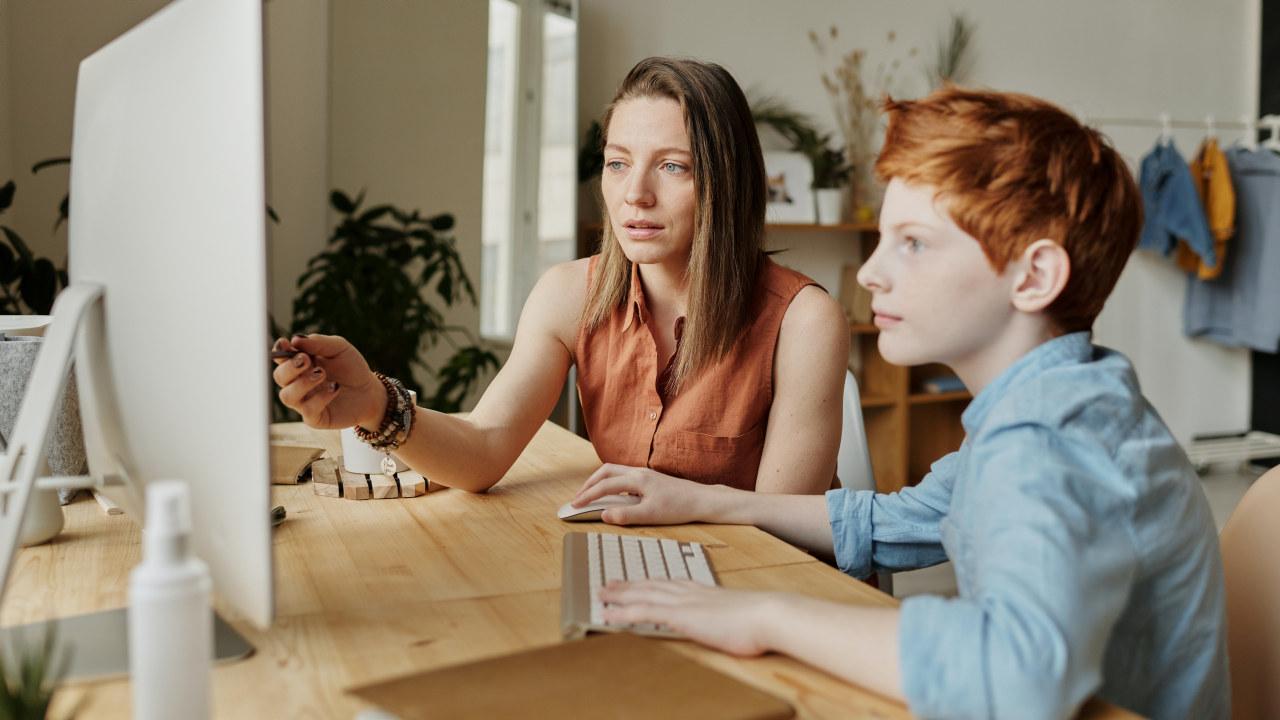 En dame og en gutt jobber sammen på en PC. Foto