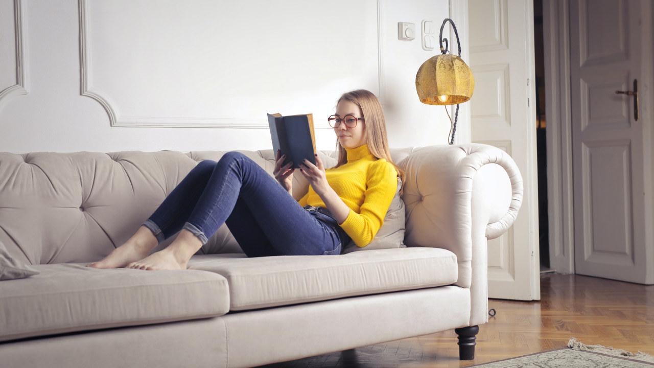 Foto: Dame ligger på sofaen og leser