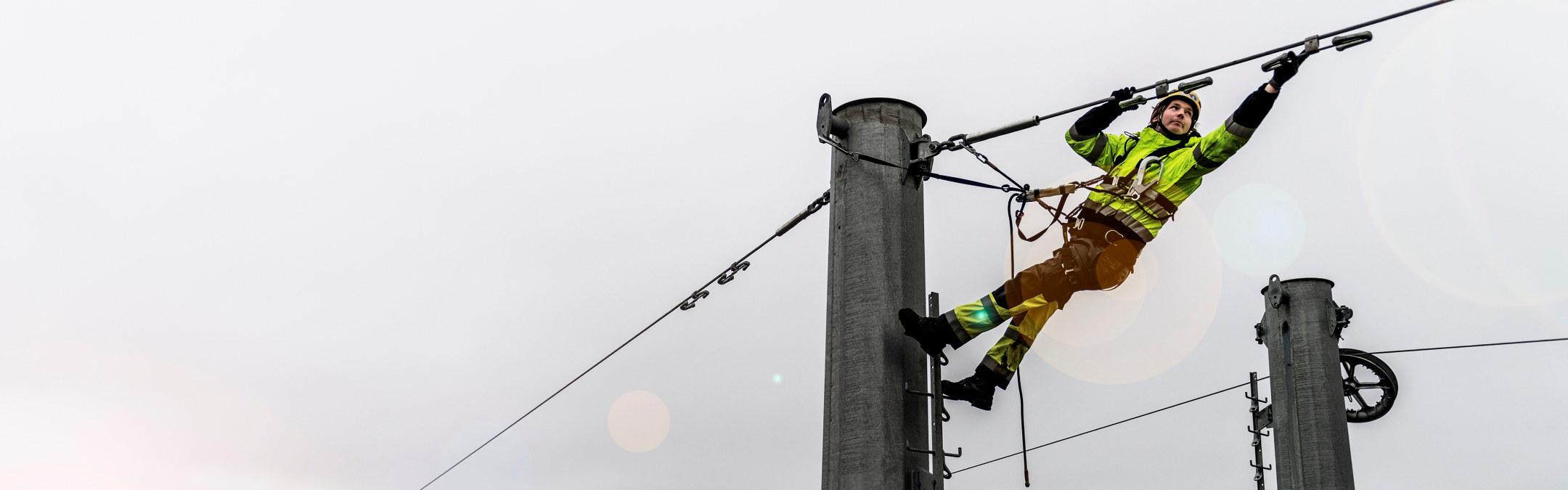 Foto: En energimontør jobber i en strømmast