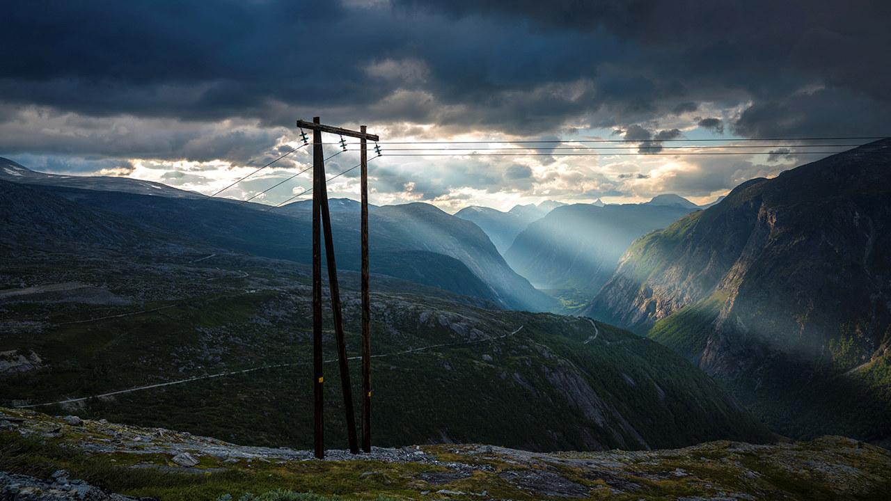 Kraftmaster omkranset av fjell. Foto