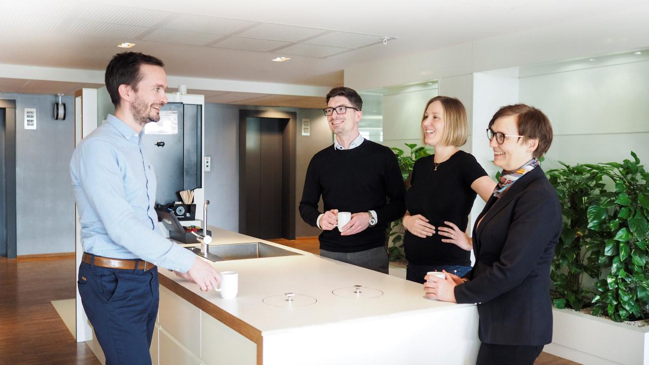 Foto: Fire kolleger står og snakker med hverandre ved kaffemaskinen