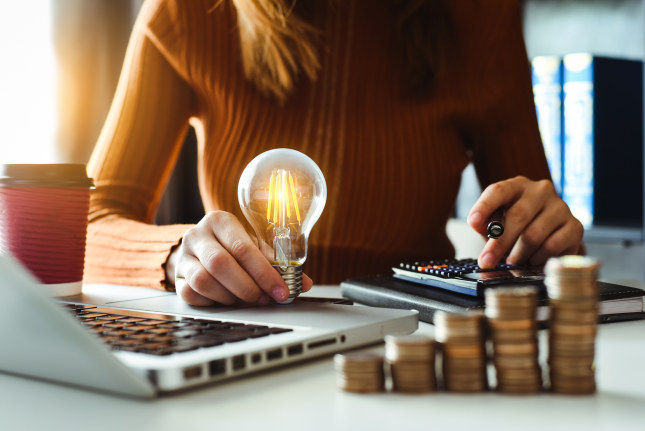 business man hand holding lightbulb with using smartphone and calculator to calculate and money stack. idea saving energy and accounting finance in morning light