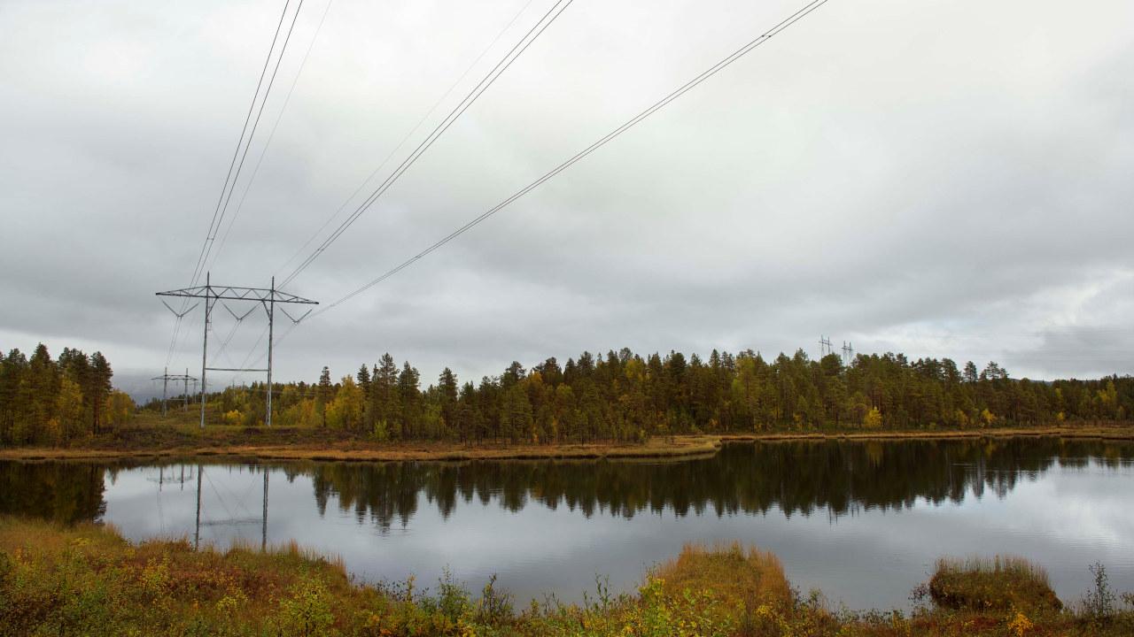 Kraftmast med linjespenn over et vann om høsten. Foto