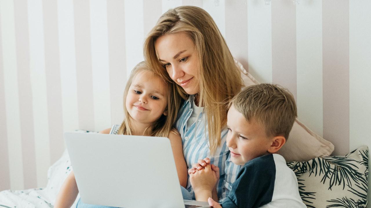 Mor med to barn ser på en PC skjerm. Foto